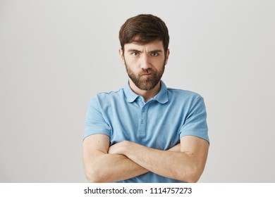 Portrait of bothered angry mature guy with beard standing with crossed hands and frowning, looking with mad expression at camera, being offended
