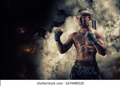 Portrait of a boxer of mixed martial arts standing on the background of smoke and fire. The concept of sports, mma, kickboxing. Mixed media