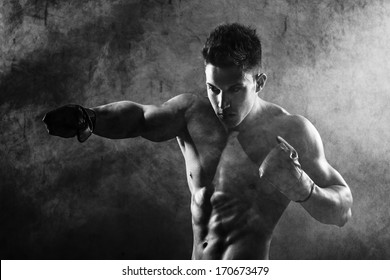 Portrait of boxer posing in studio in gloves .Photo has an intentional film grain) .Fine art.