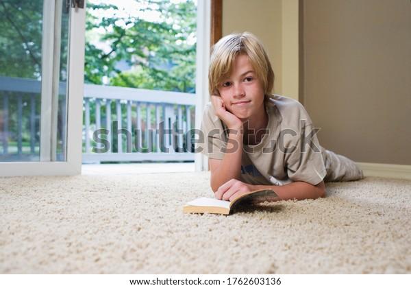 Portrait of boy (10-12) lying on carpet reading book
