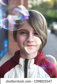 Portrait of a boy among soap bubbles on a city street