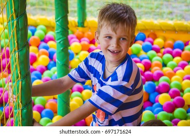 Portrait of a boy in balls on a playground.