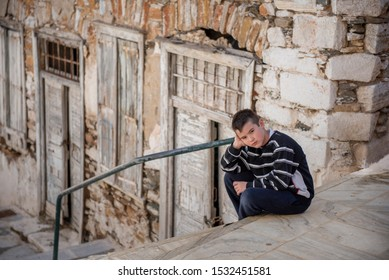 Portrait of a boy in black and white clothes posing,siting in the street of a traditional small street in Syros island,Cyclades, Aegean sea,Greece
