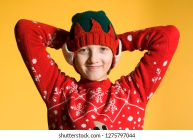 Portrait of a Boy with Blond Hair in Red Christmas Sweater Smiling.