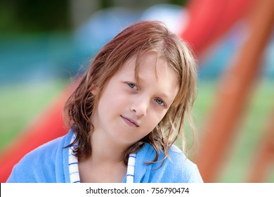 Portrait of a Boy with Blond Long Hair in Blue Robe Outdoors