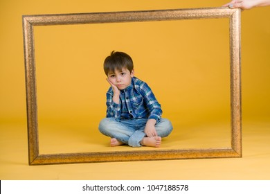 Portrait of the boy in blue shirt and jeans on the yellow background with frame. Bored.