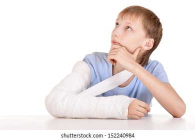 Portrait of boy with a broken arm on white background
