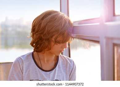 Portrait of a boy by the window. A sad boy looks out the window. Emotions of sadness and disappointment.