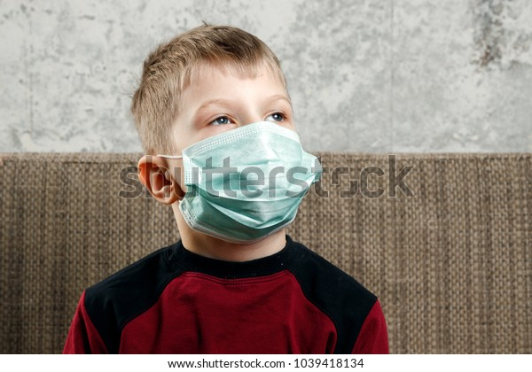 Portrait of a boy, a child in a medical mask. The concept of disease, flu in children, tuberculosis, immunity, protection from disease.