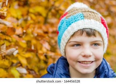 portrait of a boy with colorful autumn leaves in the background