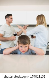 Portrait of boy covering ears while parents arguing in background at home