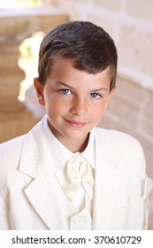 Portrait of boy doing his holy communion dressed in white wedding suite jacket