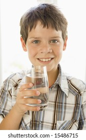 Portrait of boy drinking glass of water indoors by a window