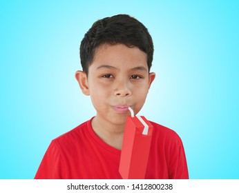 Portrait of Boy Drinking Soy Milk from UHT Box with Straw Isolated on Cyan Background