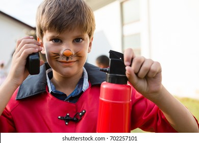 Portrait of boy with face paint using walkie talkie while holding fire extinguisher during birthday party