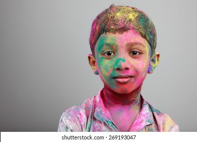 Portrait of boy with face smeared with colored powder. Concept for festival Holi