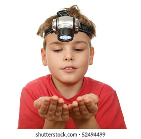 Portrait of boy with flashlight on his head on white background. Smiling, he looks at his hands.