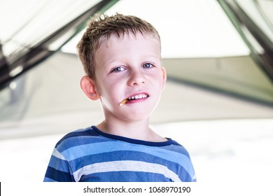 Portrait of a boy with food in his mouth. The kid eats and smiles. The boy is eating a snack.