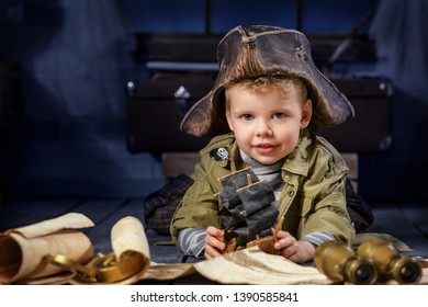 Portrait of a boy in the form of a pirate playing with a ship in his room at night