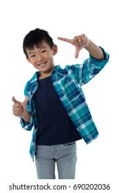 Portrait of boy forming a finger frame against white background