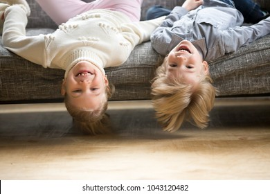 Portrait of boy and girl laughing lying upside down, happy cheerful kids brother with sister having fun together on sofa at home, head shot of smiling cute funny children siblings looking at camera