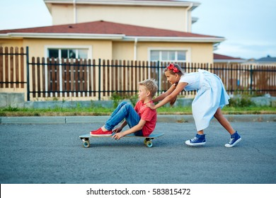 Portrait of boy and girl playing in the street: girl pushing her brother sitting on skateboard in middle of road at quiet town neighborhood