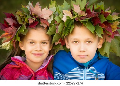 Portrait of a boy and a girl wearing wreathes of fall leaves
