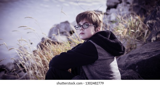 A portrait of a boy with glasses sitting on the shore against a blurry background of rocks and Autumn grasses. The boy wears a hoodie in this chilly, dark scene.
