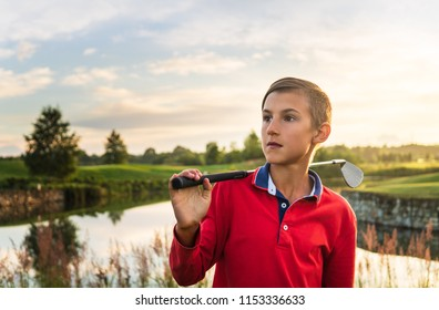 Portrait of boy golf player standing on fairway at evening at golf course