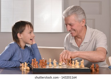 portrait of a boy and grandfather playing chess at home