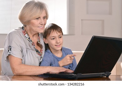 portrait of a boy and grandmother with a laptop at home