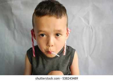 Portrait of a boy with a grey top eating lollies short hair cut. Half Asian half westerner. Black, dark hair. Candy cane hanging from his ears. Looking straight at the camera.