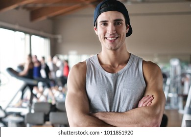 Portrait of a boy in a gym that trains his body to stay fit and have defined muscles. The athlete smiles and is happy with his workout. Concept of: sport, gym, personal trainer and fitness