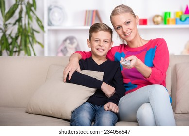 Portrait of a boy with his mom are watching TV at home.