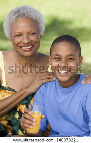 Portrait of a boy holding glass of orange juice with grandmother