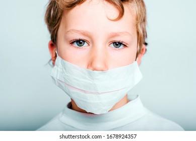 Retrato de un niño, aislado de fondo blanco, con una máscara para protegerse del virus covid-19