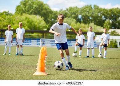 Portrait of boy in junior football team  leading ball between cones during  practice in field on sunny day