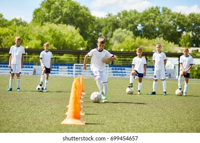 Portrait of boy in junior football team  leading ball between cones during  practice in field on sunny day with team in background