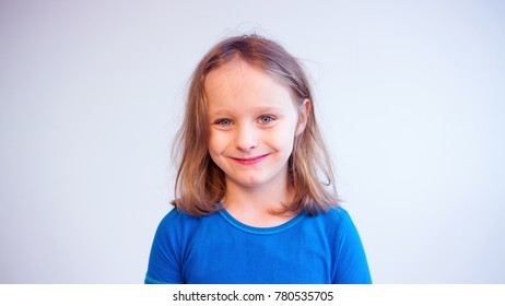 portrait of boy with long blond hair smiling at camera