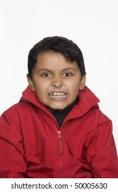 Portrait of a boy looking at the camera with a scary expression on his face. Vertical shot. Isolated on white.