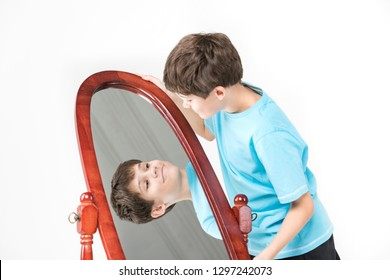 Portrait of a boy looking in a mirror on a white background.