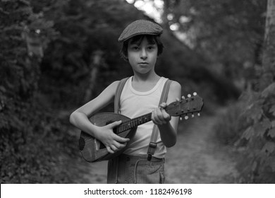 Portrait of a boy with a mandolin. Black and white.