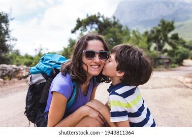 Porträt eines Jungen mit Mutter auf einem Hintergrund von Bergen, eine Frau reist mit einem Kind, ein Kind umarmt eine Mutter, ein Mädchen mit einem Rucksack wandert mit einem Kind