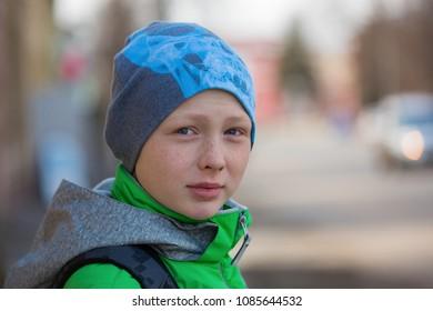 portrait of a boy on a city street