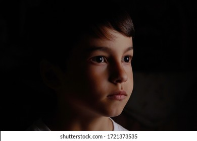 portrait of a boy on a dark background close up face