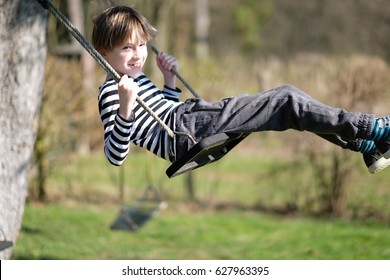Portrait of a boy on a hanging swing