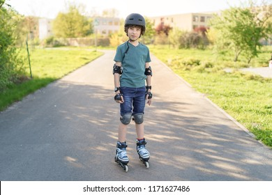 Portrait of a boy on rollers in a protective helmet, knee pads and elbow pads.