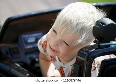 Portrait of a boy on a toy electric car