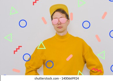 portrait of boy in pink painted sunglasses, yellow baseball cap and oversize pullover among memphis geometry figures. crazy surreal art