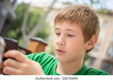 portrait of a boy playing computer games on phone